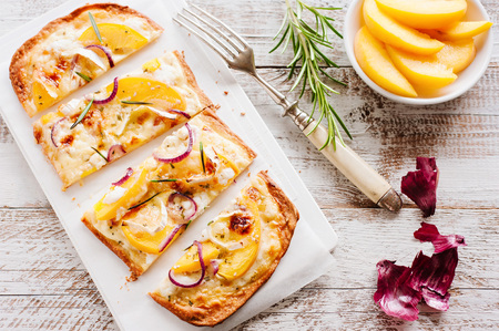 복숭아, 염소 치즈, 로즈마리 및 꿀과 함께 Tarte flambée 스톡 콘텐츠