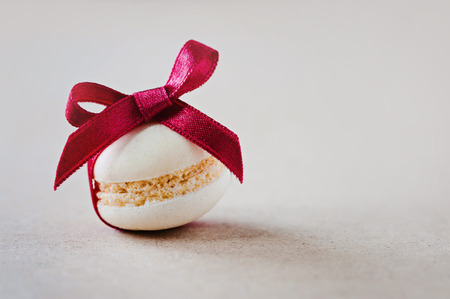 Christmas macaron with red ribbon and text space on the right Archivio Fotografico