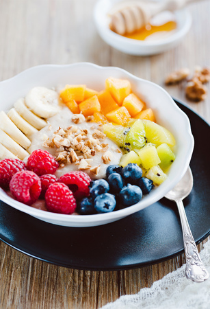 fresh porridge with mixed fruit, honey and nuts
