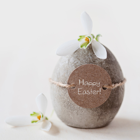 Concrete easter egg and snowdrops