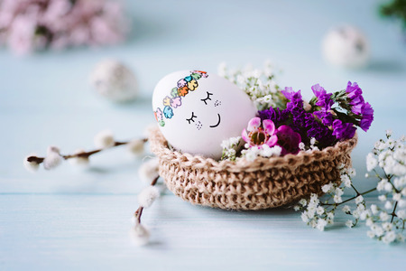 Happy Easter greetings  Little Easter egg with a sweet face in the Easter basket Stockfoto
