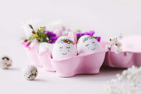 Two cute Easter eggs cuddle up in the pink Easter box with pretty flower decoration - Happy Easter!