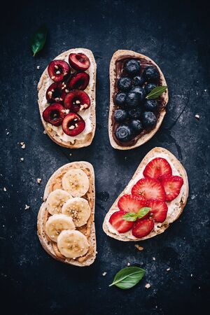 Healthy breads with fresh fruits - colorful breakfast on dark background,