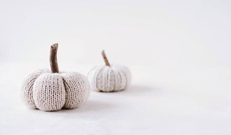 Crocheted pumpkins on neutral, light background with copy space