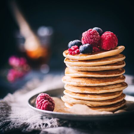 Pancakes with frosted berries and dark background