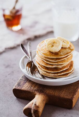 Fresh pancakes with maple syrup and bananas