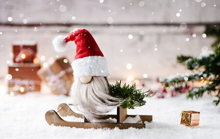 Cute santa claus on a sleigh ride - winter scene with wooden background, snow and a lot of christmas gifts Standard-Bild - 134455177