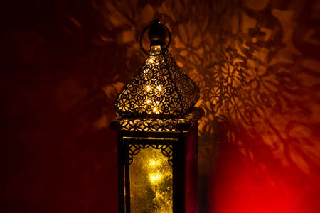 Ornamental Arabic lantern with burning light glowing at night and glittering golden bokeh lights.