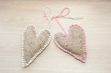 tighten: Two tighten with a rope self made linen hearts on the wooden beige table Stock Photo
