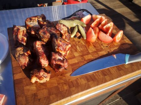 On the grill are roast pieces of meat, smoke is coming and red coals are visible