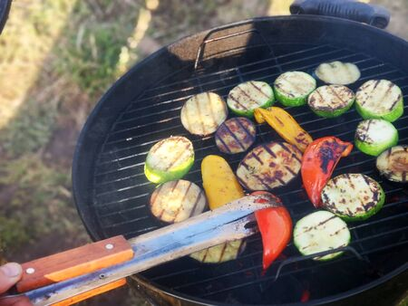On the grill are roast pieces of vegetables, smoke is coming and red coals are visible Stock fotó