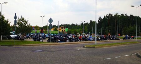 Many motorcycles of various colors and styles are parked in the same parking lot