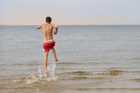 A young man jumping happily into the waters of the Baltic Sea in Jurmala, Latvia