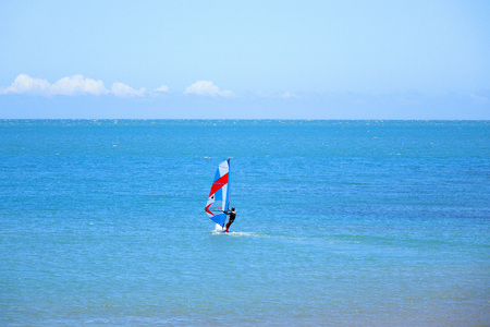 windsurfing: A man windsurfing at sea