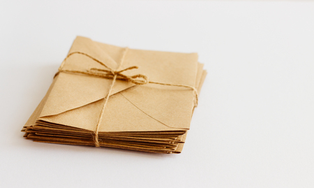 Mail kraft envelopes on white background, closeup. A stack of letters wrapped in twine.