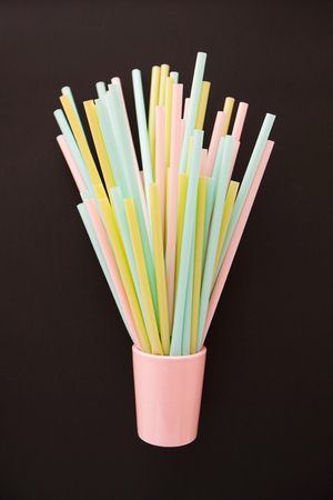 A bunch of colorful pastel plastic straws in a pink glass on a black background.