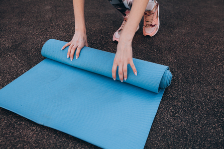 Close-up of attractive young woman folding blue yoga or fitness Mat after training at the stadium. A healthy lifestyle, keep yourself in the form of a concept. Stock Photo