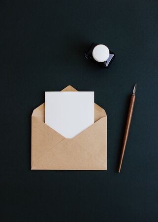 On a black background, an empty white card with an envelope of Kraft paper, fountain pen and inkwell are on a black background.