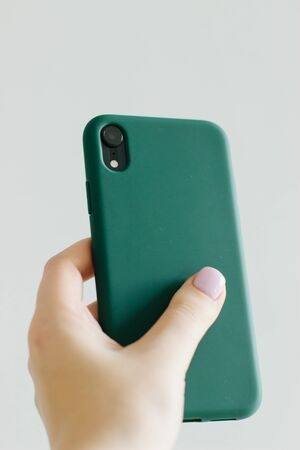 Smartphone on a light background with dark green silicone cover on the back. Template the body of the phone.