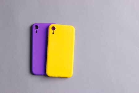 Colorful silicone cases for your smartphone. Bright yellow and purple silicone cases for smartphone. Flat lay. 写真素材