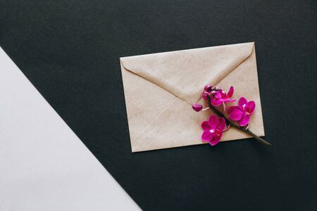 Envelope made of environmentally friendly brown material. Simple brown paper envelopes for letters. Purple Orchid flowers for decoration. The layout for the design.