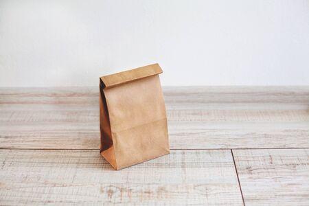 Bolsa de papel sobre suelo de madera clara. Bolsa de papel marrón simple para el almuerzo o la comida. El diseño para el diseño. Paquetes de barcos ambientales.
