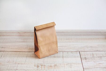Paper bag on light wooden floor. Simple brown paper bag for lunch or meal. The layout for the design. Environmental ship packages.