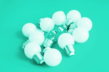 A lot of bulbs in trend mint tonic. Lamps on a mint background. A large set of led bulbs. A burned out incandescent bulb and led energy-saving light bulbs are on the light surface. Stock Photo