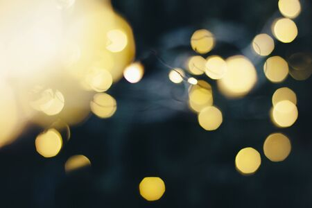 A beautiful image of a bokeh from New Years garlands. In gold colors. Defocused glitter lighting image for art and design.