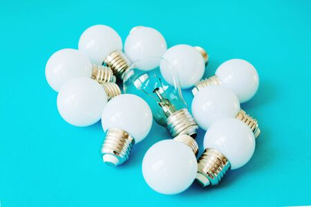 Lamps, LED lamps and fluorescent lamps on blue background. Large set of LED bulbs. White energy-saving light bulbs. Light bulbs lie in a row.