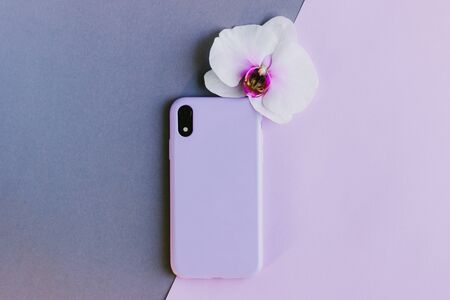 Lilac silicone case on grey and pink background. Pastel purple silicone case for smartphone. Protection for the back cover of the mobile phone with a slot for the camera. Orchid flower.