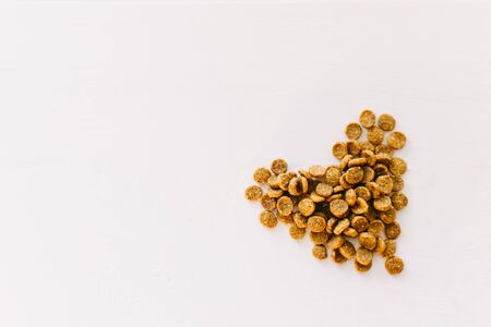 Dry pet food laid out on a white wooden background in the shape of a heart. Food for sterilized cats or dogs. Hypoallergenic food. Selective focus.