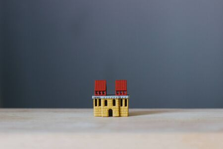 Model house on a wooden surface. A miniature house with a red roof on a wooden layout on a blurred gray background. Images on real estate investment idea. Stockfoto
