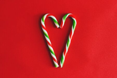 Two candy canes making a heart on a red textured background. Candy cane heart. Christmas candy canes.