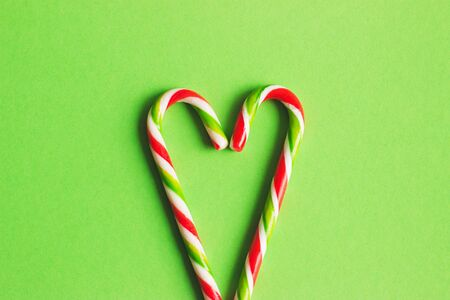 Two candy canes making a heart on a green textured background. Candy cane heart. Christmas candy canes.