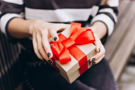 Girl with gift box in her hands. Female in a striped jumper holds out a gift tied with a satin red ribbon. Gift for Christmas, birthday, Valentine's day.