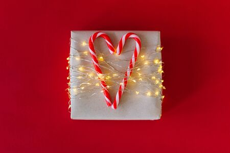 Gift box on bright red background. Christmas striped candy canes. The gift is tied with led tape. Two lollipops are connected in the heart. Candy heart. Christmas garland. Selective focus.