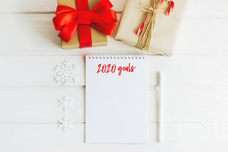 Christmas composition. Notepad with goals for 2020. Notepad, pen, gift boxes, letter envelopes, wooden snowflakes and stars. Christmas striped candy canes. Selective focus.