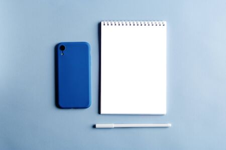 An empty notebook, a smartphone in a blue case, a white pen on pastel background. White page, top view, flat lay. 免版税图像