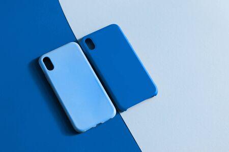 Coques en silicone pour smartphone en deux tons de bleu. Couleur de l'année 2020 Bleu Classique. Étuis de protection en silicone pour téléphone. Mise au point sélective.