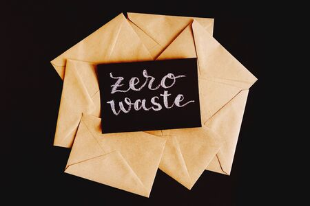 Lots of Kraft envelopes and zero waste lettering. Envelopes for letters isolated on a black background. Imagens