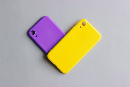 Protective silicone covers are purple and yellow on a grey background. Two silicone cases for the smartphone. Heart shape. Stok Fotoğraf