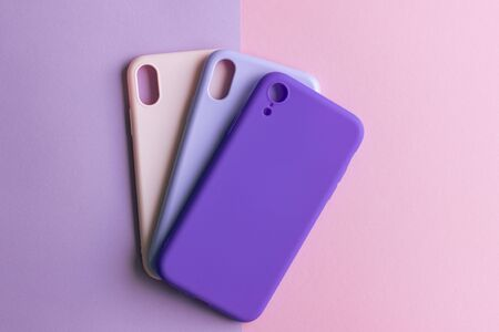 Pink, lilac and purple cases for the smartphone on the grey background. Protective silicone cases for smartphone. Colorful silicone cases for your smartphone.