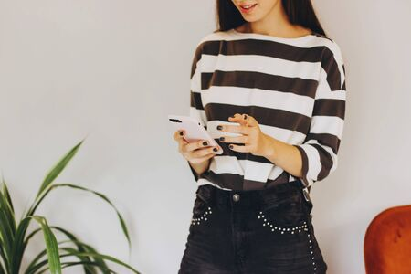 A girl in a striped jacket and dark jeans with rivets holds a smartphone in a pink case. A girl prints a message on her phone. Selective focus.