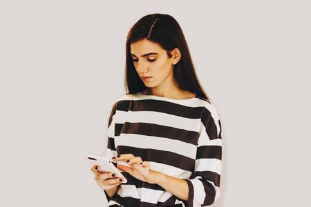 A girl in a striped sweater holds a smartphone in her hands. The girl is typing a message on her phone. Girl on a gray background. Selective focus.