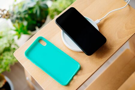Black smartphone and mint silicone case is charged from a wireless charger. The mobile phone is charged on a wooden nightstand or shelf.