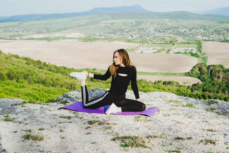 Yoga classes in the open air. Outdoor sports. A beautiful athlete in the mountains. Sports during quarantine and self-isolation.