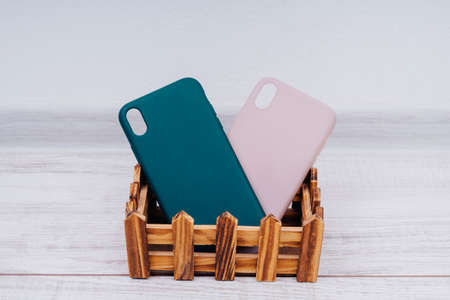 Silicon covers on a smartphone in a wooden box. Green and beige smartphone cases.