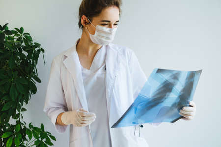 A radiologist in a medical mask and gloves radiates an x-ray image of the patients lungs. The girl doctor works on the front line. The doctor is holding an X-ray of his lungs.