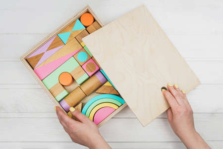 Wooden constructor for children. A box of childrens wooden designer in his hands. Colorful toys made of natural materials. Zero waste.